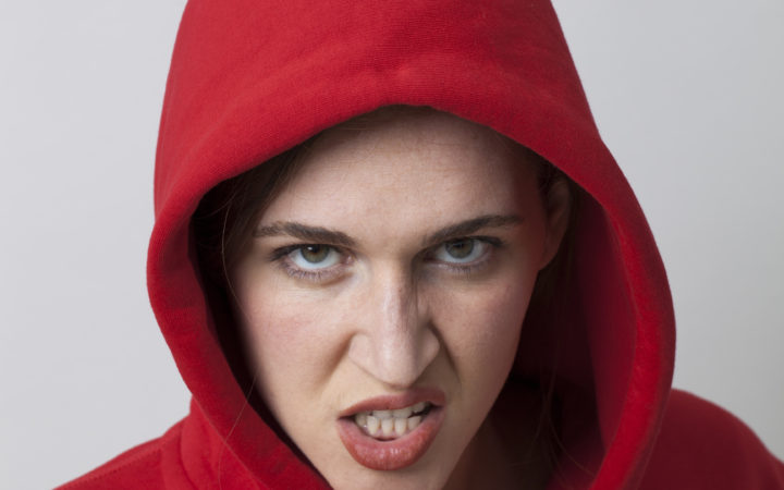 female threat concept - rebellious 20s girl wearing streetwear with hooded sweater expressing hatred and rage,closeup in studio